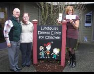 Presenting a check Madigan Foundation to Lindquist Dental